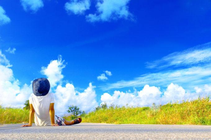 青空が広がる草原の一本道に座る少年